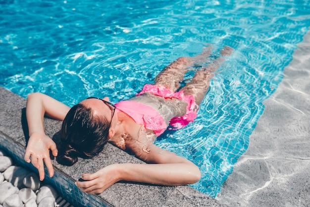 Giovane bella donna che gode delle vacanze estive nella piscina di lusso