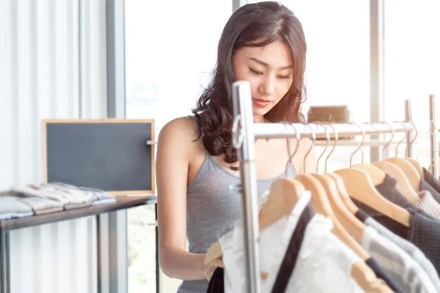 Giovane bella donna che gode nello shopping al negozio di abbigliamento