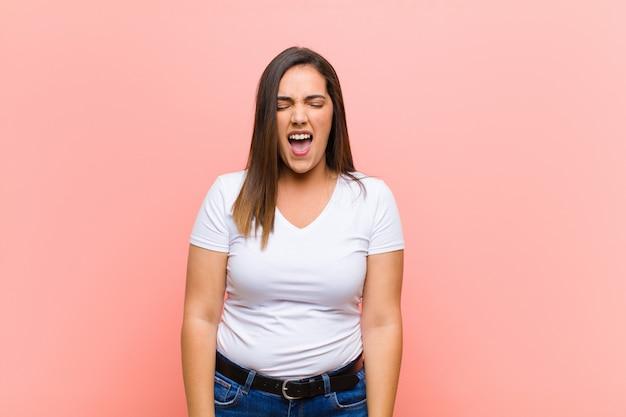 Giovane bella donna che grida in modo aggressivo, sembra molto arrabbiata, frustrata, oltraggiata o infastidita, urla sul muro rosa