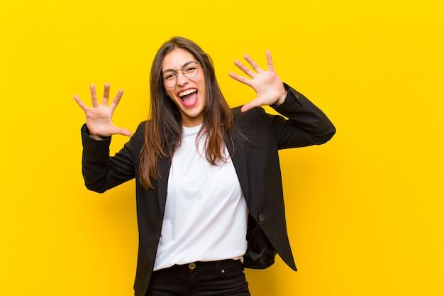 Giovane bella donna che grida in preda al panico o alla rabbia, scioccata, terrorizzata o furiosa, con le mani accanto alla testa sul muro arancione