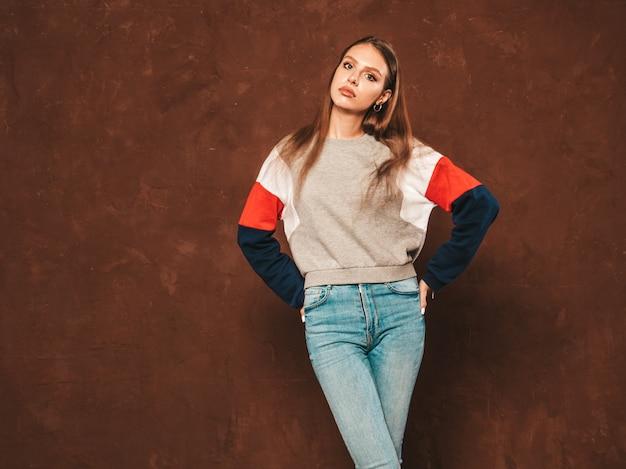 Giovane bella donna che guarda l'obbiettivo. ragazza alla moda in abiti casual camicia estiva con trucco naturale. femmina positiva. modello divertente che posa vicino alla parete blu in studio