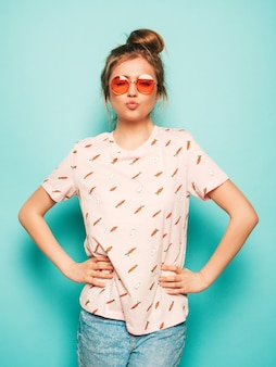 Giovane bella donna che guarda l'obbiettivo. ragazza alla moda in abiti casual t-shirt estiva fa la faccia di anatra. la femmina positiva mostra le emozioni facciali. modello divertente isolato sul blu in occhiali da sole