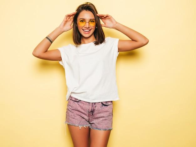 Giovane bella donna che guarda l'obbiettivo. ragazza alla moda in pantaloncini di maglietta e jeans bianchi estivi casual in occhiali da sole rotondi. la femmina positiva mostra le emozioni facciali. modello divertente isolato su giallo