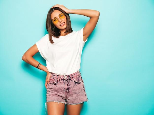 Giovane bella donna che guarda l'obbiettivo. ragazza alla moda in pantaloncini di maglietta e jeans bianchi estivi casual in occhiali da sole rotondi. la femmina positiva mostra le emozioni facciali. modello divertente isolato sul blu