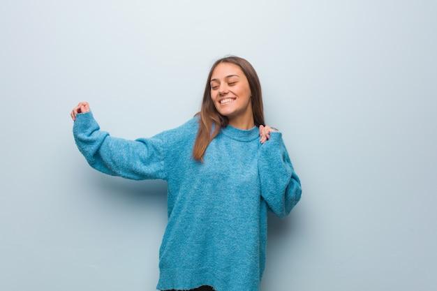 Giovane bella donna che indossa un maglione blu ballare e divertirsi