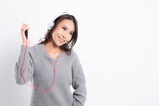 Giovane bella donna che indossa un maglione grigio è sdraiato e ascolta la musica indossando le cuffie bianche di musica isolate su priorità bassa bianca