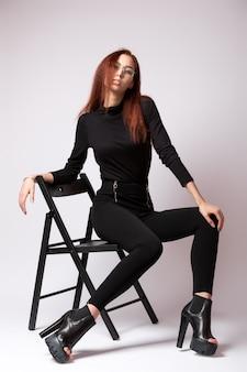 Giovane bella donna che indossa un poloneck nero, jeans neri e stivali su tacchi alti in posa sulla sedia