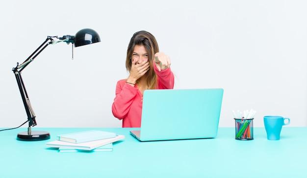 Giovane bella donna che lavora con un computer portatile ridendo di te, indicando la fotocamera e prendendo in giro o prendendoti in giro