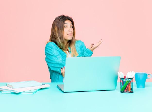 Giovane bella donna che lavora con un computer portatile sentendosi confusa e senza sensi, chiedendosi una spiegazione o un pensiero dubbioso