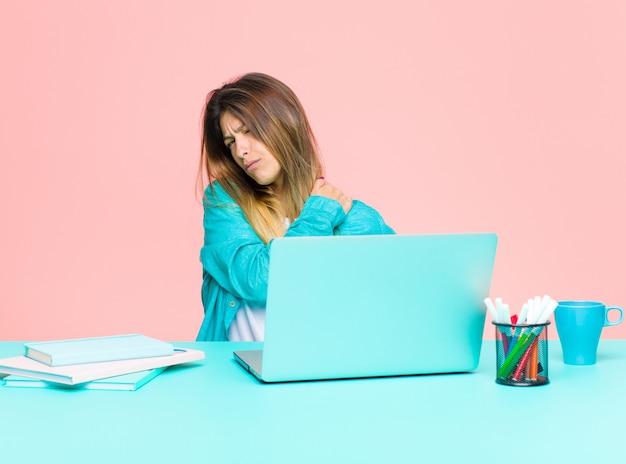 Giovane bella donna che lavora con un computer portatile sentirsi stanchi, stressati, ansiosi, frustrati e depressi, con dolore alla schiena o al collo