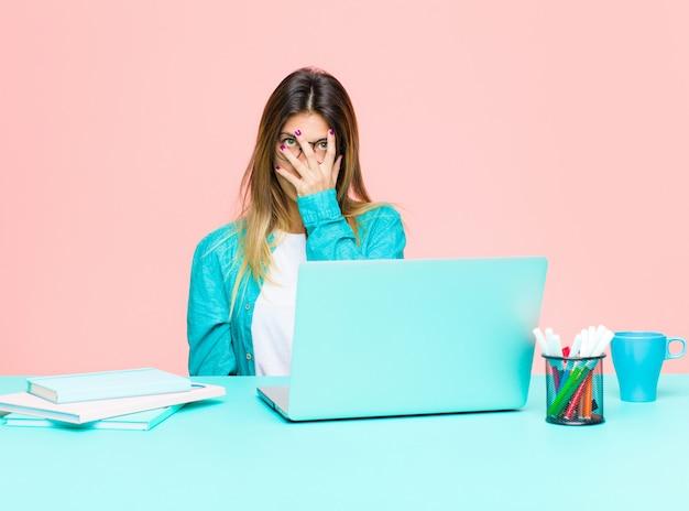 Giovane bella donna che lavora con un laptop annoiato, frustrato e assonnato dopo un compito noioso, noioso e noioso, tenendo il viso con la mano
