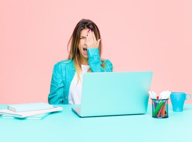 Giovane bella donna che lavora con un laptop dall'aspetto assonnato, annoiato e sbadigliante, con un mal di testa e una mano che copre metà del viso