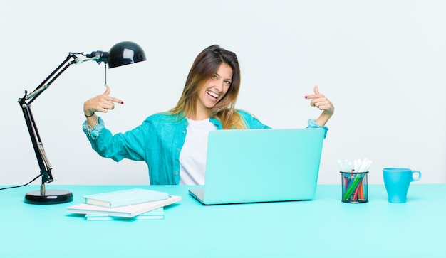 Giovane bella donna che lavora con un laptop dall'aspetto orgoglioso, arrogante, felice, sorpreso e soddisfatto, indicando se stesso, sentendosi come un vincitore
