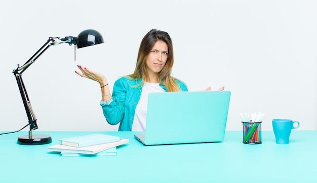 Giovane bella donna che lavora con un laptop dall'aspetto perplesso, confuso e stressato, chiedendosi tra diverse opzioni, sentendosi incerto