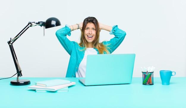 Giovane bella donna che lavora con un laptop sensazione stressata, preoccupata, ansiosa o spaventata, con le mani sulla testa, in preda al panico per errore