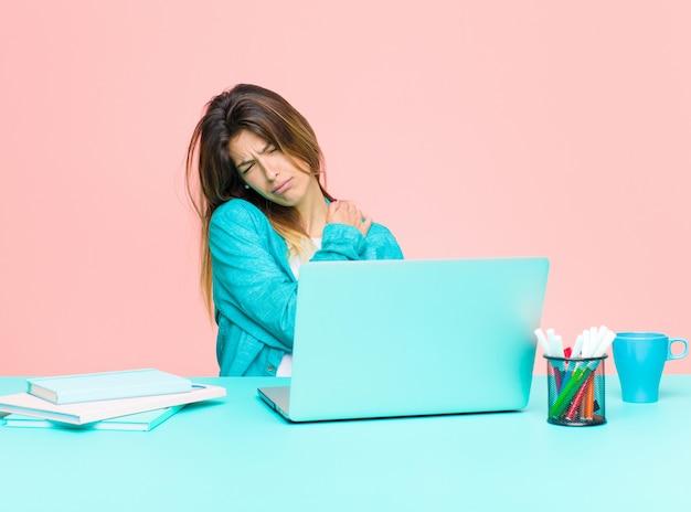 Giovane bella donna che lavora con un laptop sentendosi ansioso, malato, malato e infelice, soffrendo di dolori di stomaco o influenza