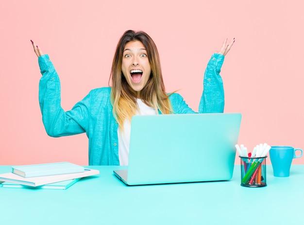 Giovane bella donna che lavora con un laptop sentendosi felice, stupito, fortunato e sorpreso, celebra la vittoria con entrambe le mani in alto