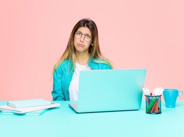 Giovane bella donna che lavora con un laptop sentendosi triste e lamentosa con uno sguardo infelice, piangendo con un atteggiamento negativo e frustrato