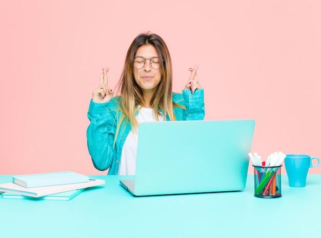 Giovane bella donna che lavora con un laptop sorridendo e attraversando ansiosamente entrambe le dita, sentendosi preoccupata e desiderando o sperando in buona fortuna