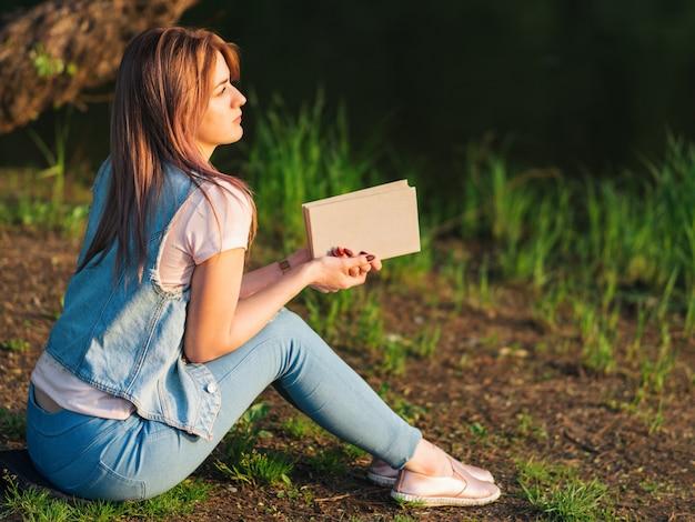 Giovane bella donna che legge un libro sulla sponda del fiume durante il tramonto