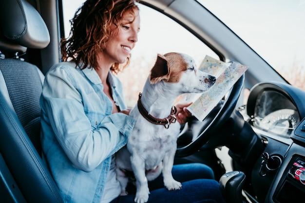 Giovane bella donna che legge una mappa in un'automobile. concetto di viaggio. simpatico jack russel cane inoltre.