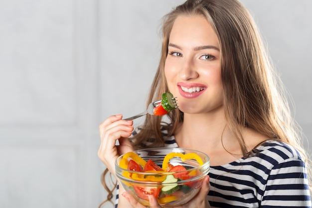Giovane bella donna che mangia alimento sano