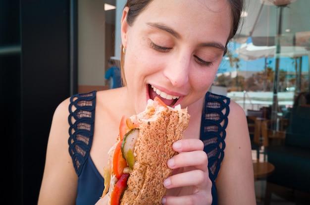 Giovane bella donna che mangia un panino