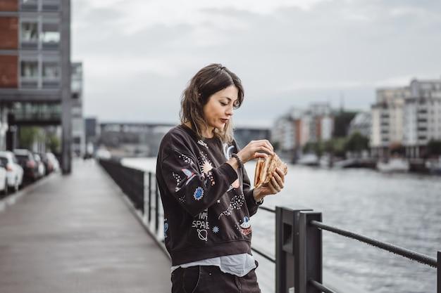 Giovane bella donna che mangia una fetta di pizza sulla via della città