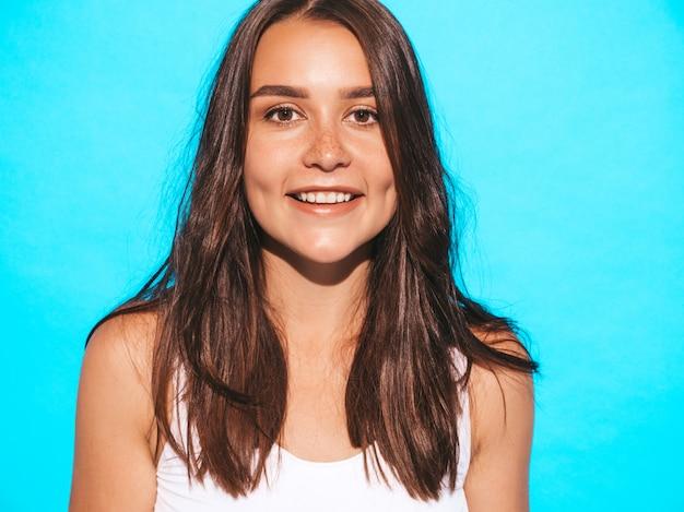 Giovane bella donna che osserva. ragazza alla moda in abiti estivi casual. posa femminile divertente e positiva vicino alla parete blu