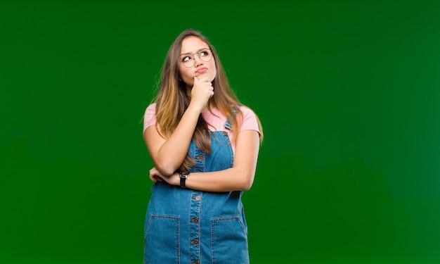 Giovane bella donna che pensa, si sente dubbiosa e confusa, con diverse opzioni, chiedendosi quale decisione prendere contro la parete verde