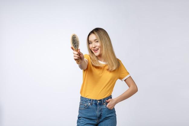 Giovane bella donna che pettina i suoi capelli isolati sopra priorità bassa grigia.