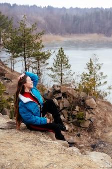 Giovane bella donna che posa su un lago