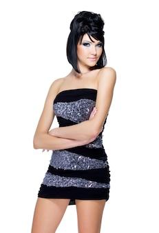 Giovane bella donna che posa sul bianco. fronte di bellezza con trucco saturo blu e acconciatura moderna