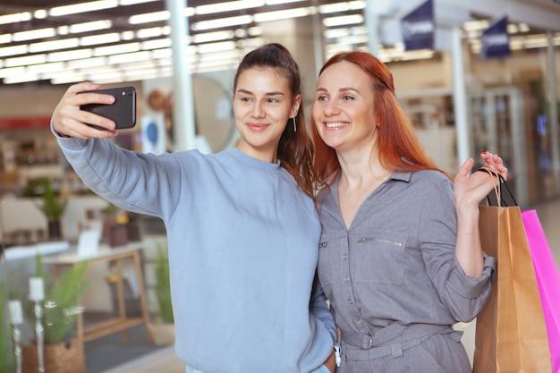 Giovane bella donna che prende selfie con il suo amico mentre compera insieme al centro commerciale