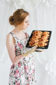 Giovane bella donna che prepara i cornetti fatti in casa