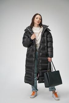 Giovane bella donna che propone in un cappotto lungo di inverno su una priorità bassa bianca