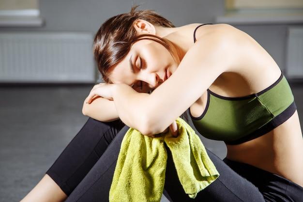 Giovane bella donna che riposa dopo un allenamento