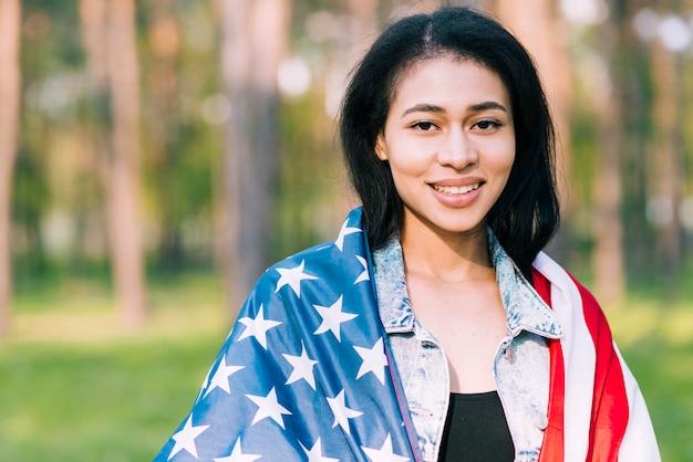 Giovane bella donna che si avvolge nella bandiera americana all'esterno