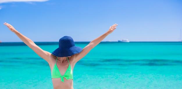 Giovane bella donna che si distende alla spiaggia tropicale sabbiosa bianca