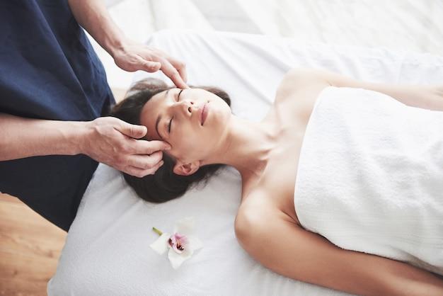 Giovane bella donna che si distende dal massaggio viso