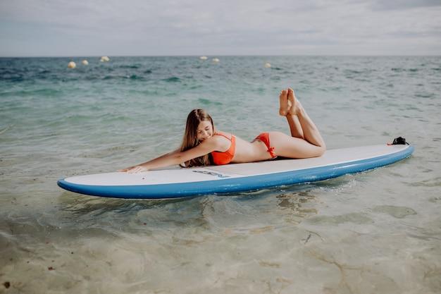 Giovane bella donna che si distende nel mare su una tavola di sup.