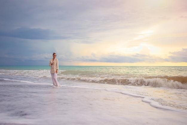 Giovane bella donna che si distende sulla spiaggia al tramonto
