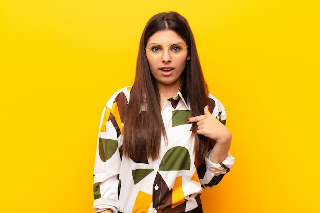 Giovane bella donna che si sente confusa, perplessa e insicura, indicando se stessa chiedendosi e chiedendo chi, io? contro il muro giallo