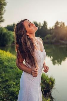 Giovane bella donna che si sente libero e felice a piedi dal fiume estivo al tramonto ammirando il paesaggio
