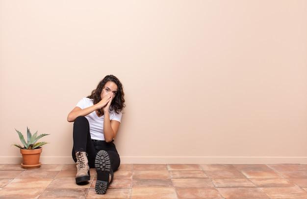 Giovane bella donna che si sente preoccupata, fiduciosa e religiosa, pregando fedelmente con i palmi premuti, chiedendo perdono seduto su un pavimento della terrazza