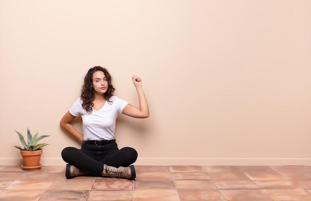 Giovane bella donna che si sente seria, forte e ribelle, alza il pugno, protesta o combatte per la rivoluzione seduta sul pavimento di una terrazza