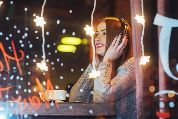 Giovane bella donna che si siede nella caffetteria, bere caffè. modella l'ascolto di musica. natale, capodanno, san valentino, vacanze invernali