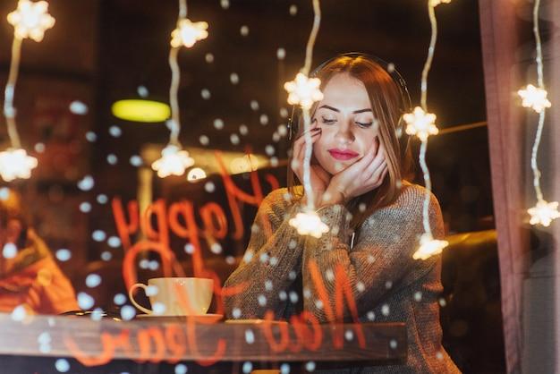 Giovane bella donna che si siede nella caffetteria, bere caffè. modella l'ascolto di musica.
