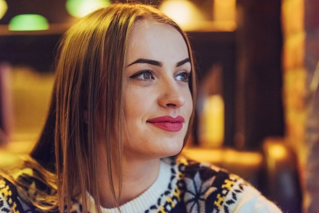 Giovane bella donna che si siede nella caffetteria, bere caffè. modello che osserva in su. natale, capodanno, san valentino, vacanze invernali
