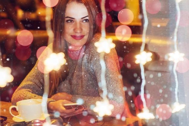 Giovane bella donna che si siede nella caffetteria, bere caffè. natale, capodanno, san valentino, vacanze invernali